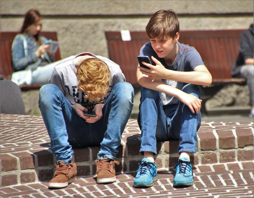 Image of two boy sitting on brown floor while using their smartphones