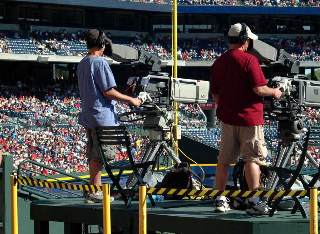 2 Camera Man Standing in a Green Metal Stage during Daytime