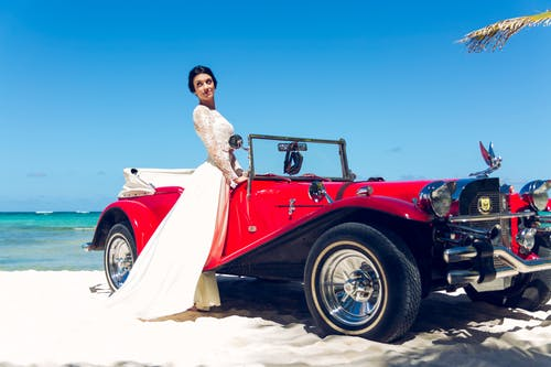 Photo of Woman Standing Near Classic Car
