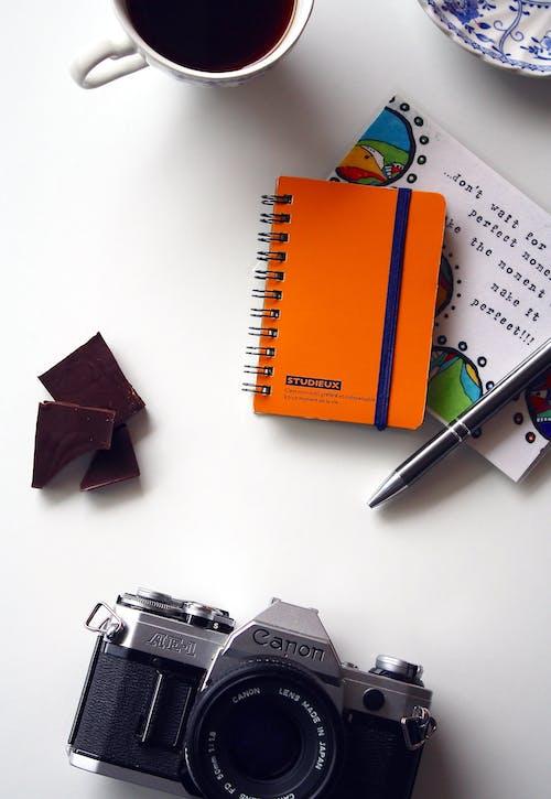 Foto d'estoc gratuïta de bloc de notes, boli, cafè, càmera