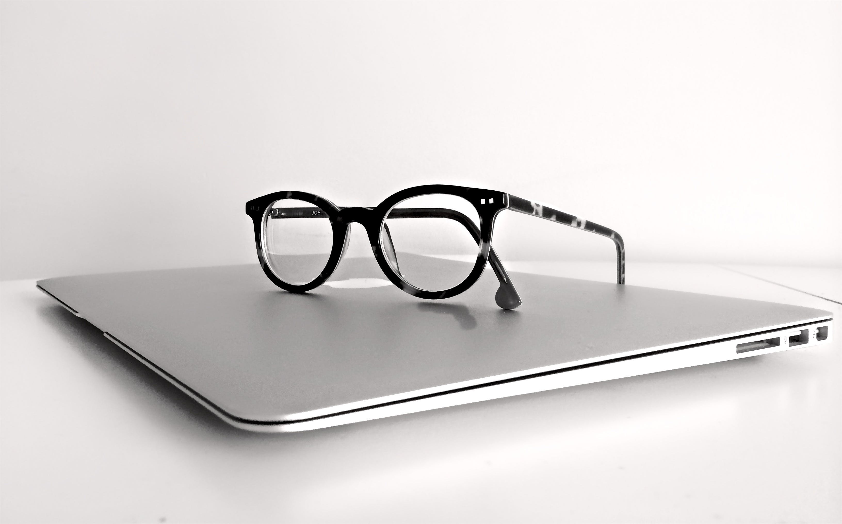 Black Frame Eyeglasses on Silver Macbook Air