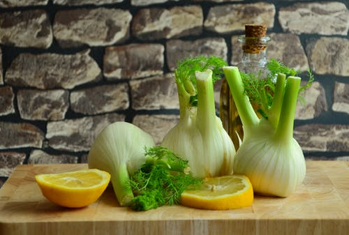 Green and White Onions and Sliced Lemons on a Brown Surface