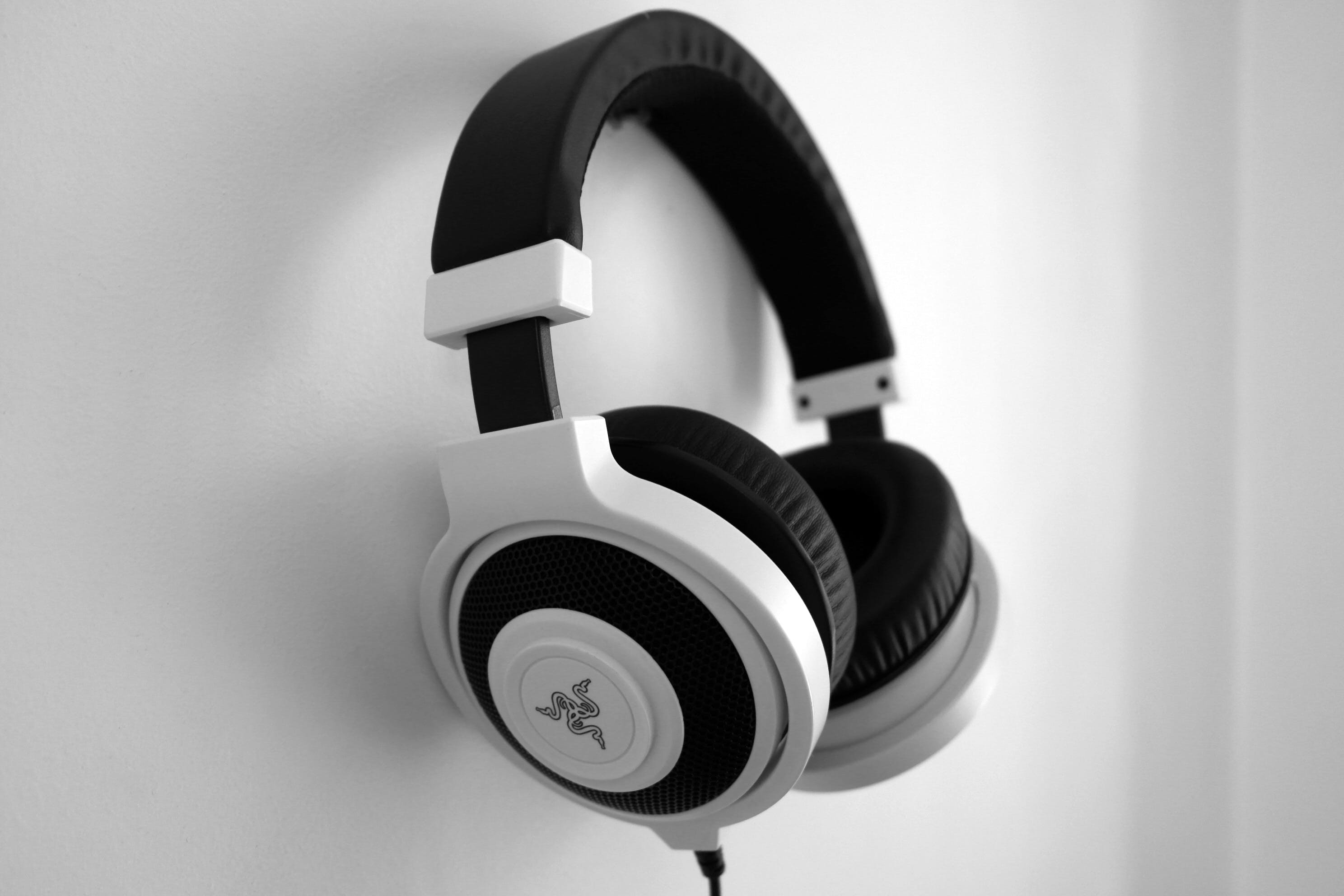 Black and White Razer Gaming Headset Hanging on White Painted Wall