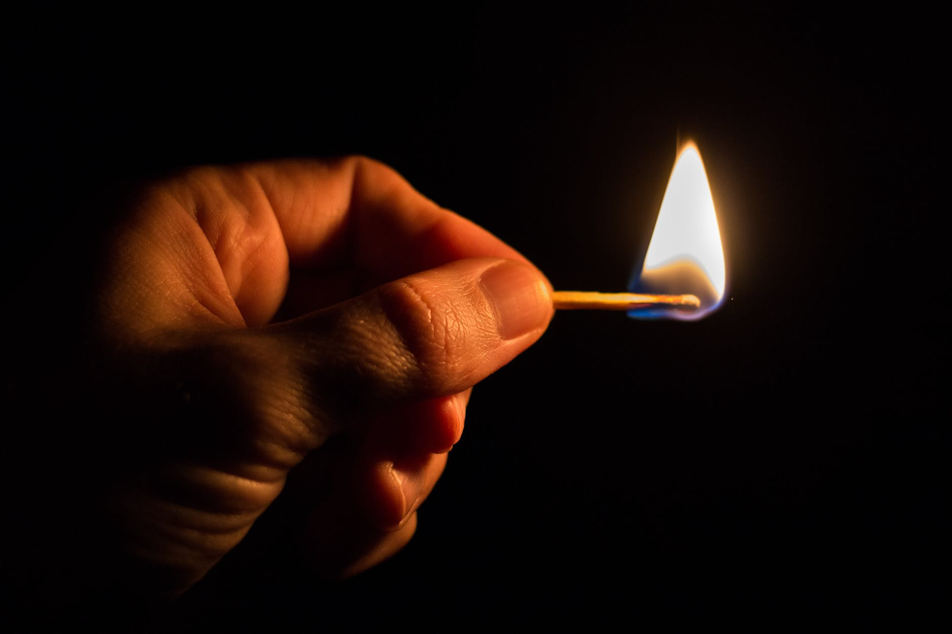 A hand holds a burning match with a black background