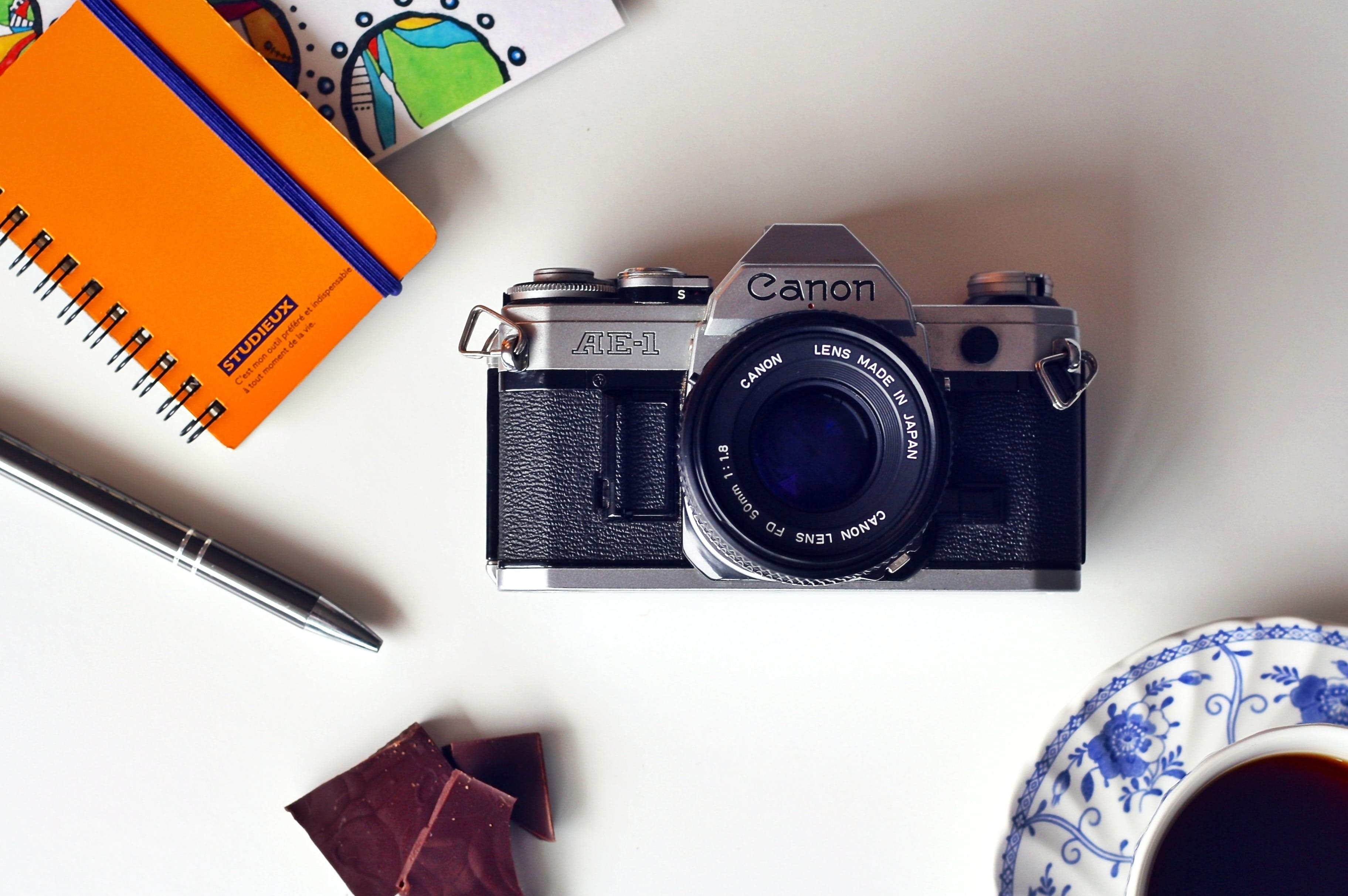 Gray and Black Canon Mirrorless Camera Beside Blue and White Ceramic Plate