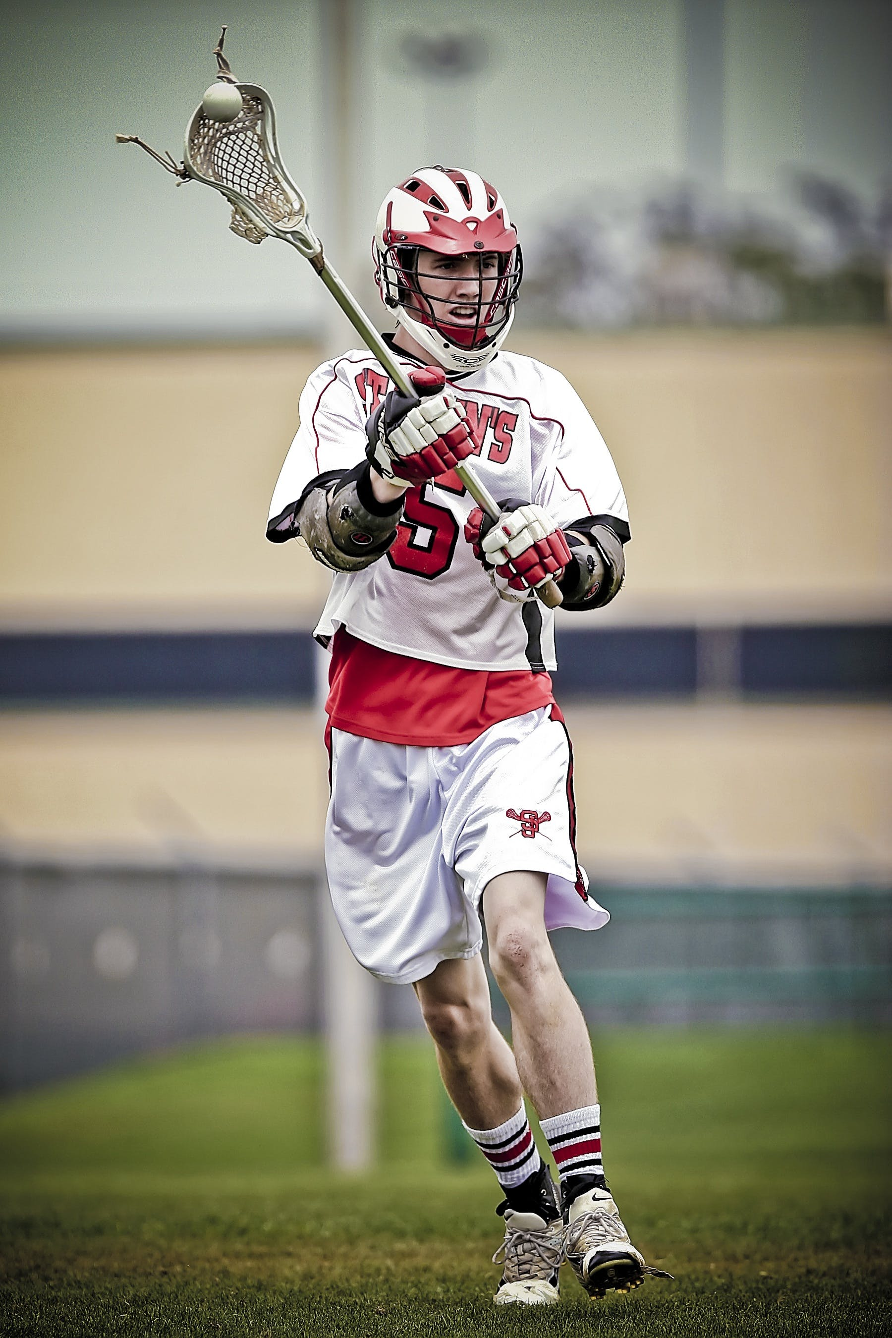 Person Holding Lacrosse Stick during Daytime