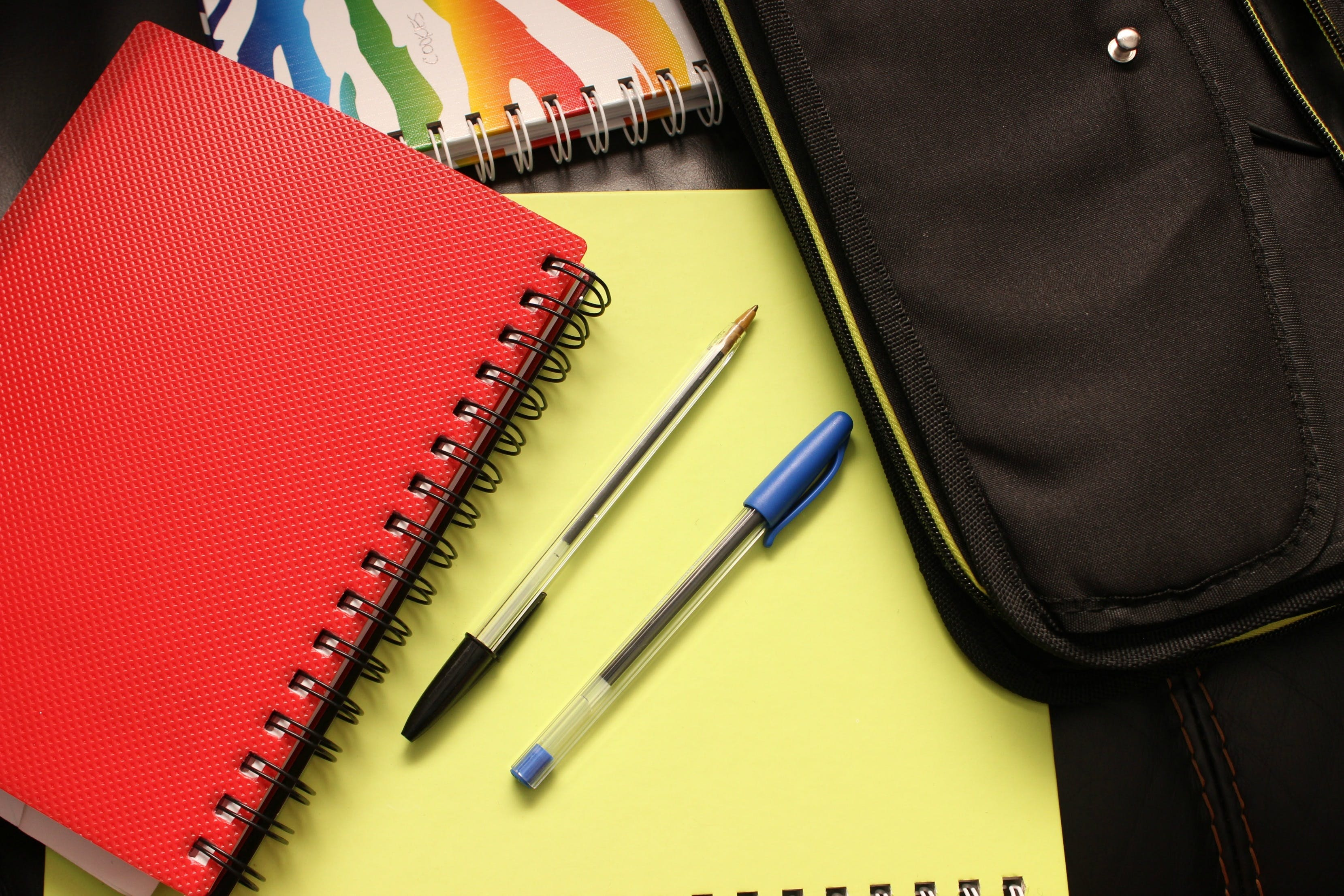 Black and Blue Pens Beside Red Covered Notebook