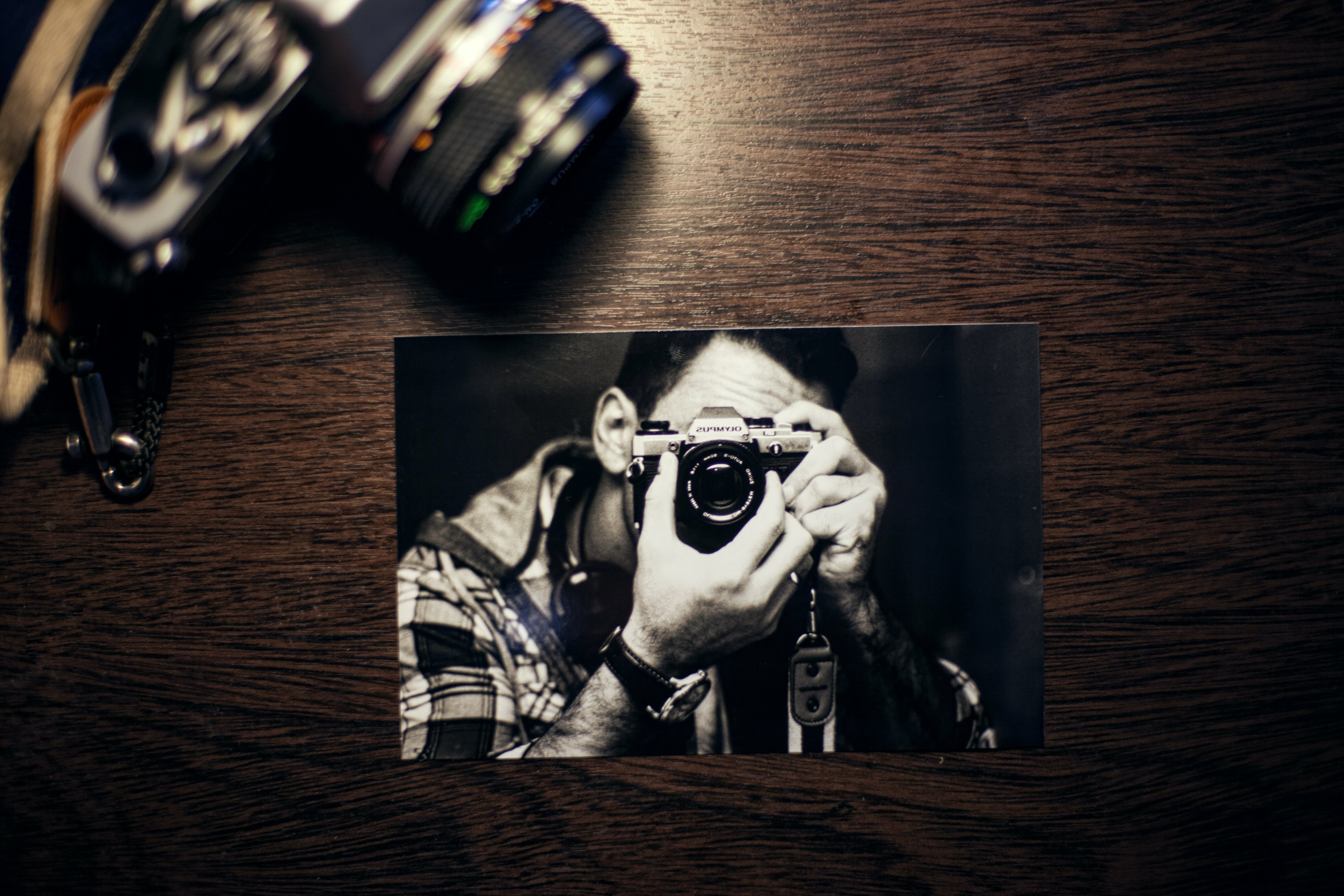 Person Using Camera Photo on Brown Surface