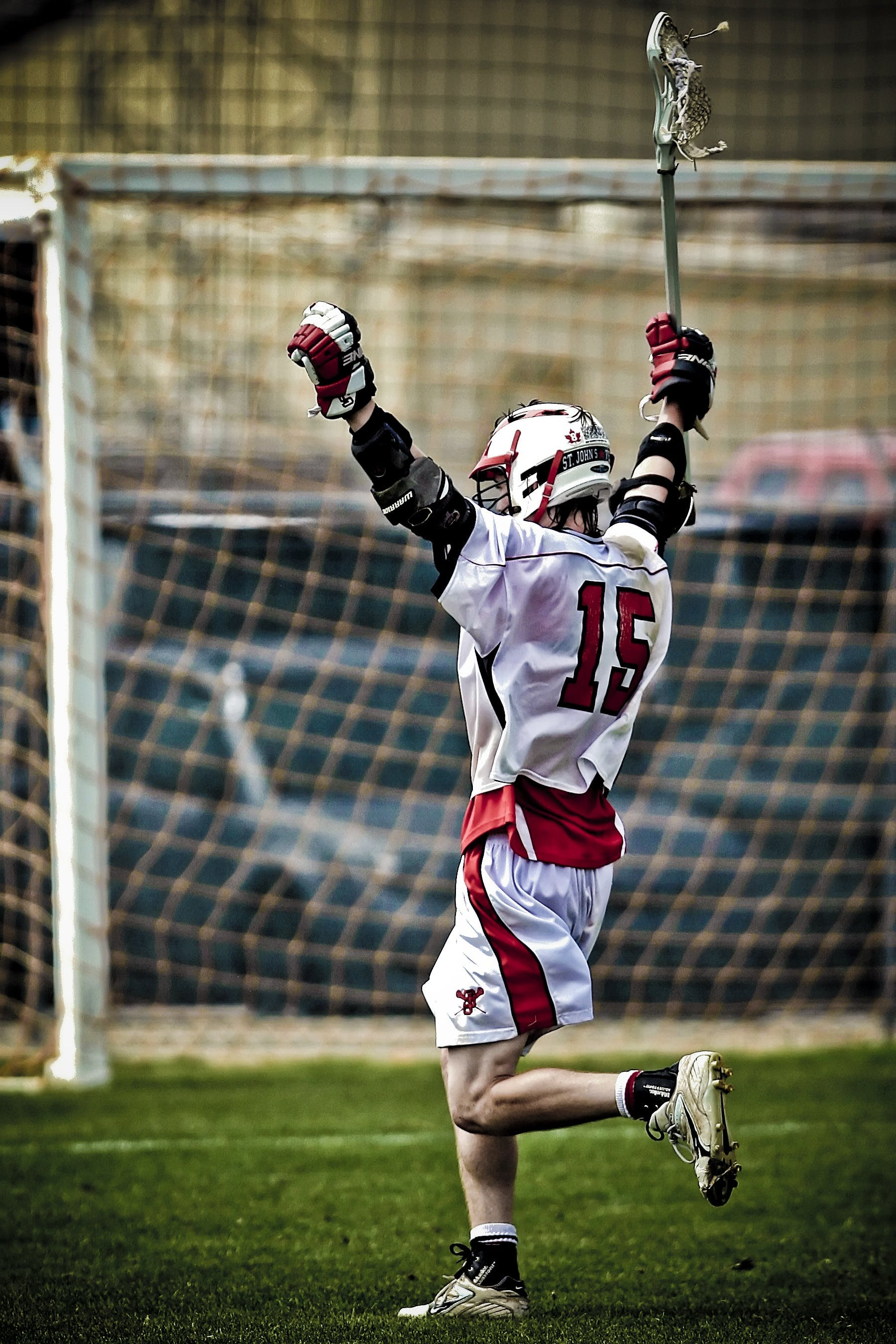 Man Holding Lacrosse Running Towards Goal