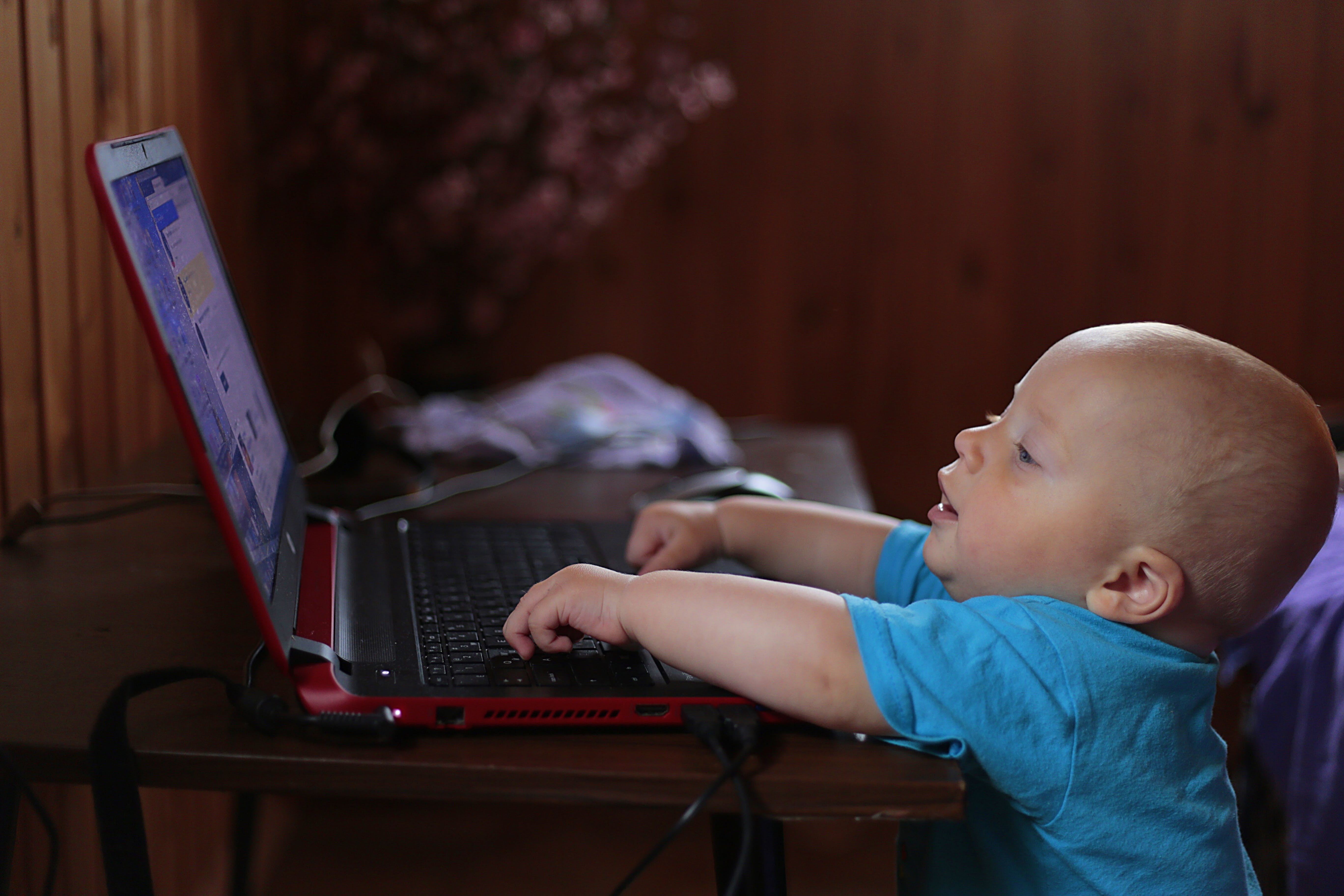 Boy Wearing Blue T Shirt Using Black Laptop Computer in a Dim Lighted Scenario