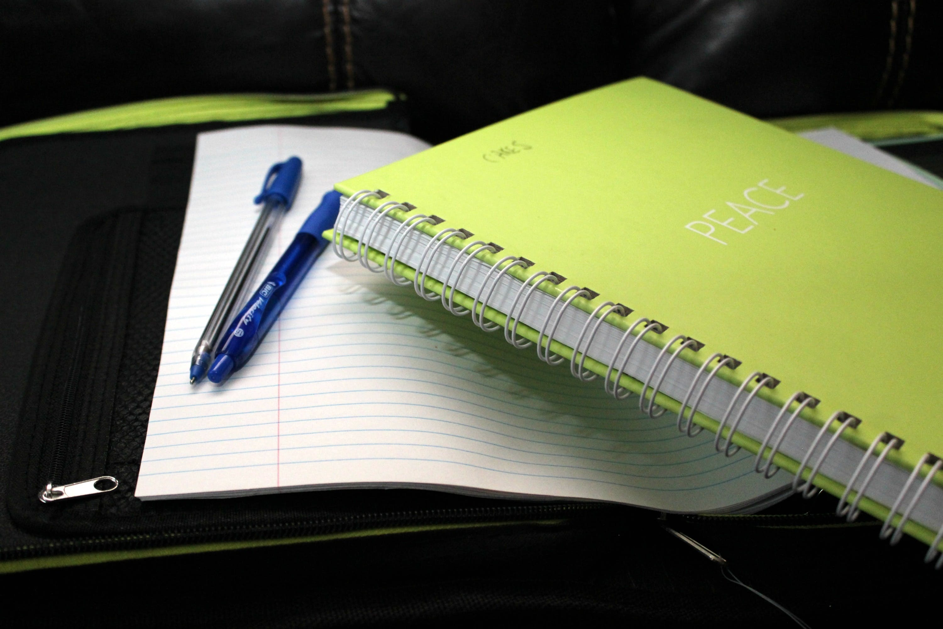 Green Spring Bind Book Beside 2 Blue Pens