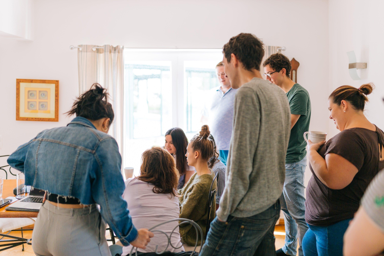 Five People Standing Near Four People Sitting Near Desk