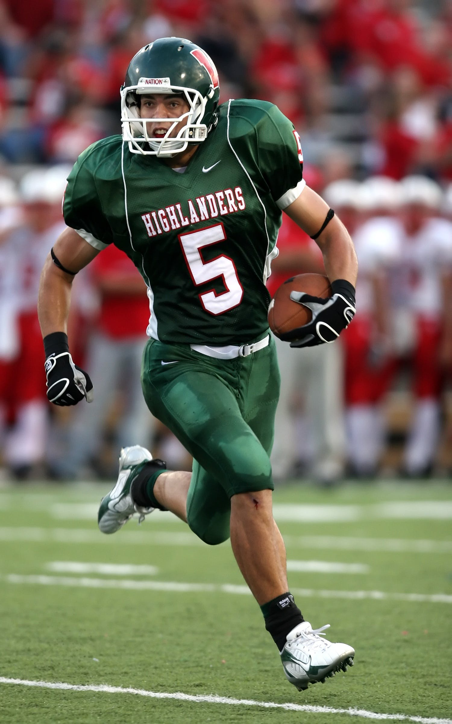 Man Wearing Green American Football Jersey Holding the Ball While Running on the Field