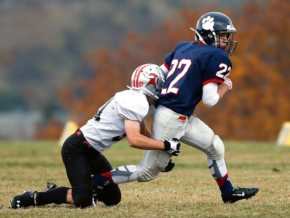 Football Player in White Trying to Stop a Player in Blue