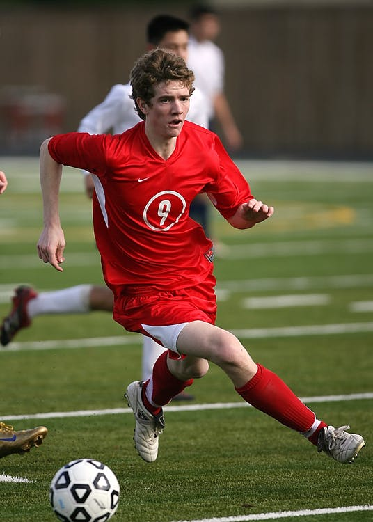 Man in Red Nike Jersey Shirt Playing Soccer