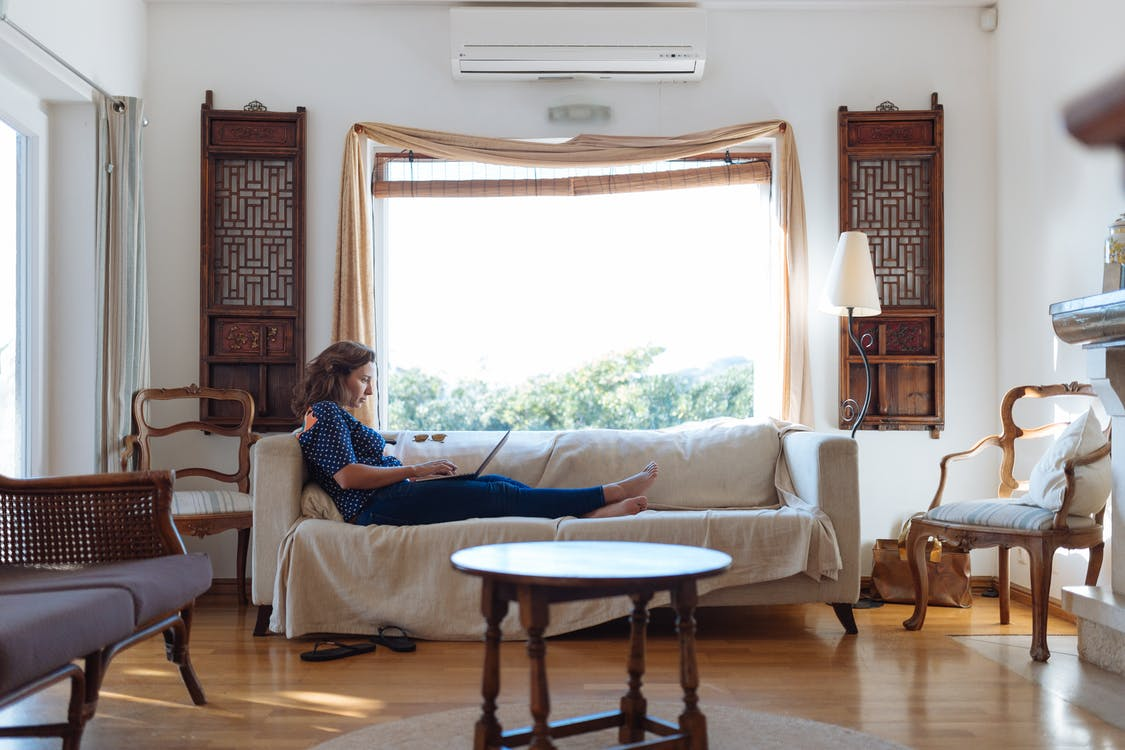 Woman Sitting on Sofa in Living Room