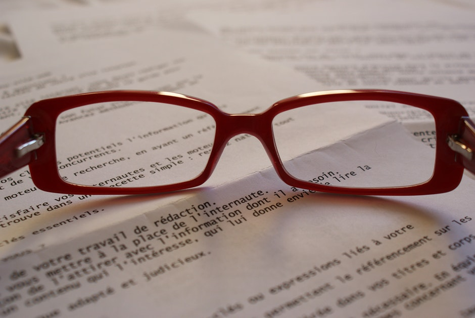 Red Framed Eyeglass on Top of Paper