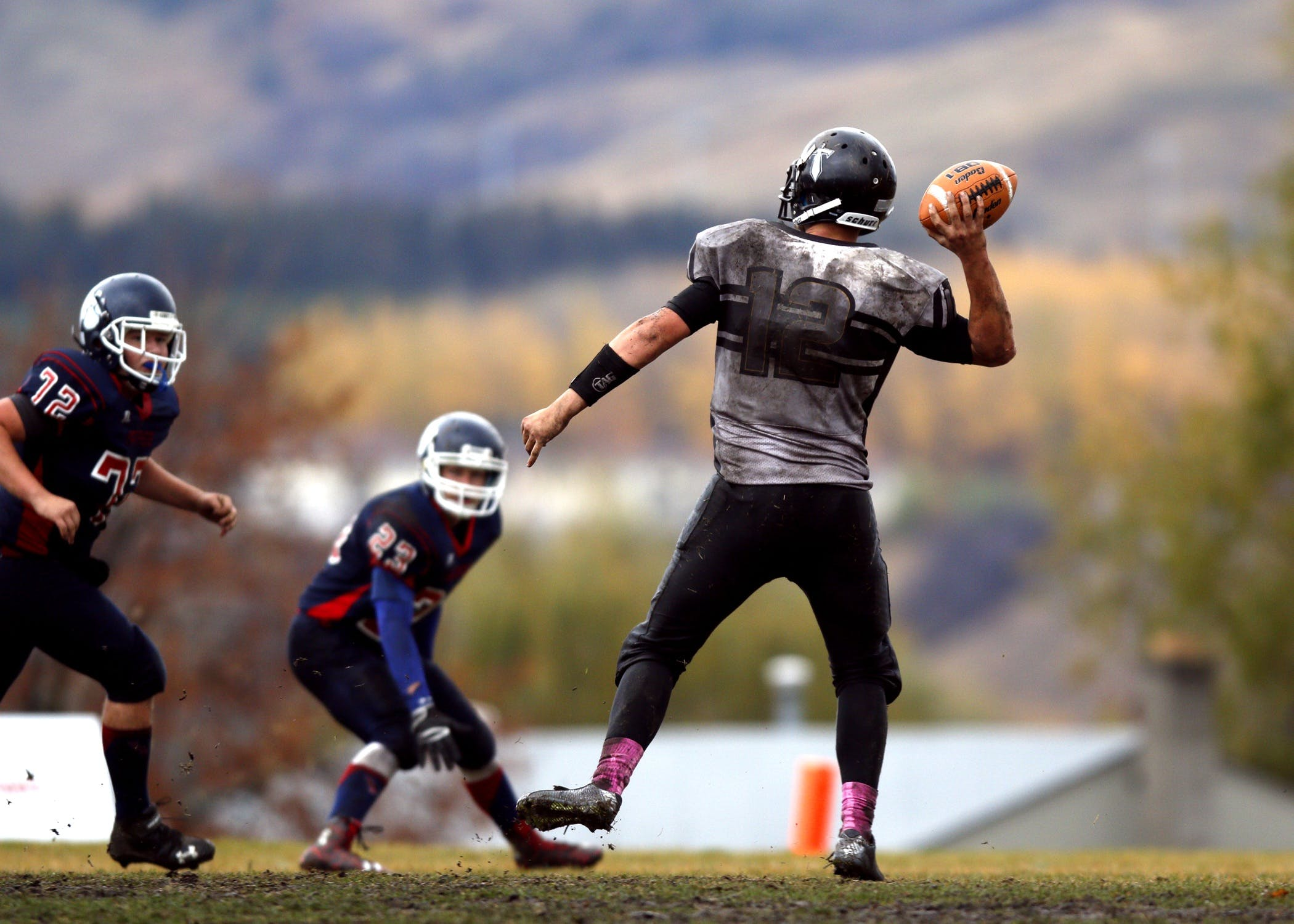2 Football Player Running After Person Holding Football during Daytime in Shallow Focus Photography