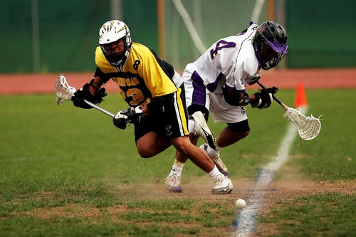 Man Wearing Yellow and Black Sport Jersey Holding Lacrosse Stick