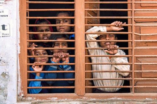 5 People Leaning on Brown Railings of Window