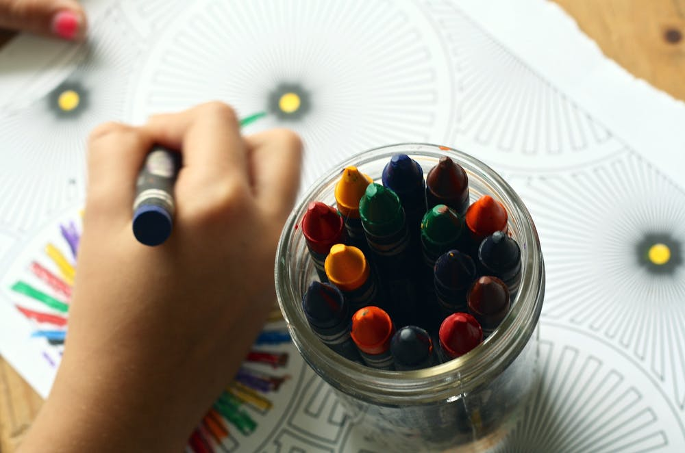 A student coloring art with crayons. | Photo: Pexels