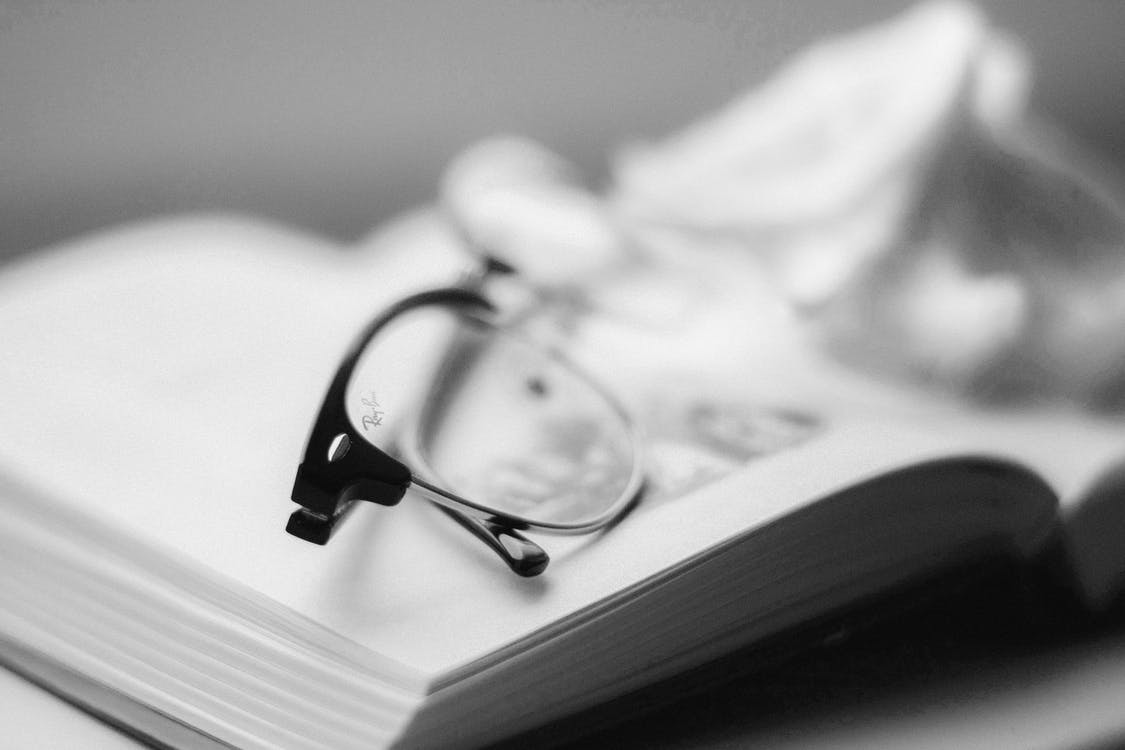 Eyeglasses With Black Frames on top of Book