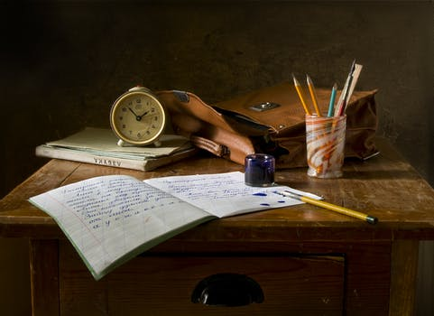An image of a desk cluttered with a bag and writing materials.