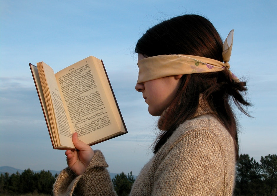 Woman Holding a Book While Her Head is Blindfolded