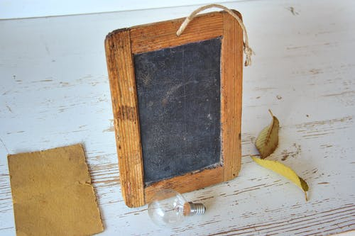 Brown Rectangular Wooden Picture Frame Near Light Bulb