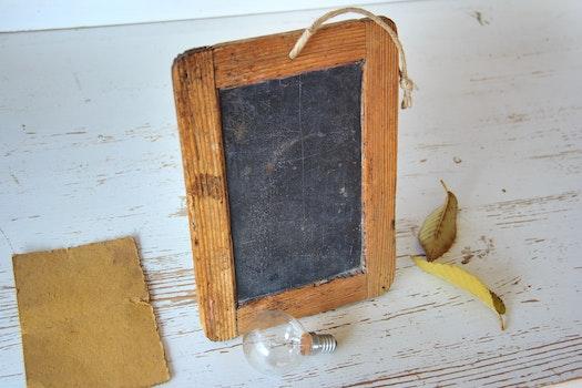 Brown Rectangular Wooden Picture Frame Near Light Bulb