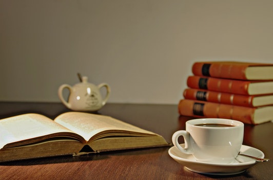White Ceramic Teacup on Brown Wooden Table Beside Book