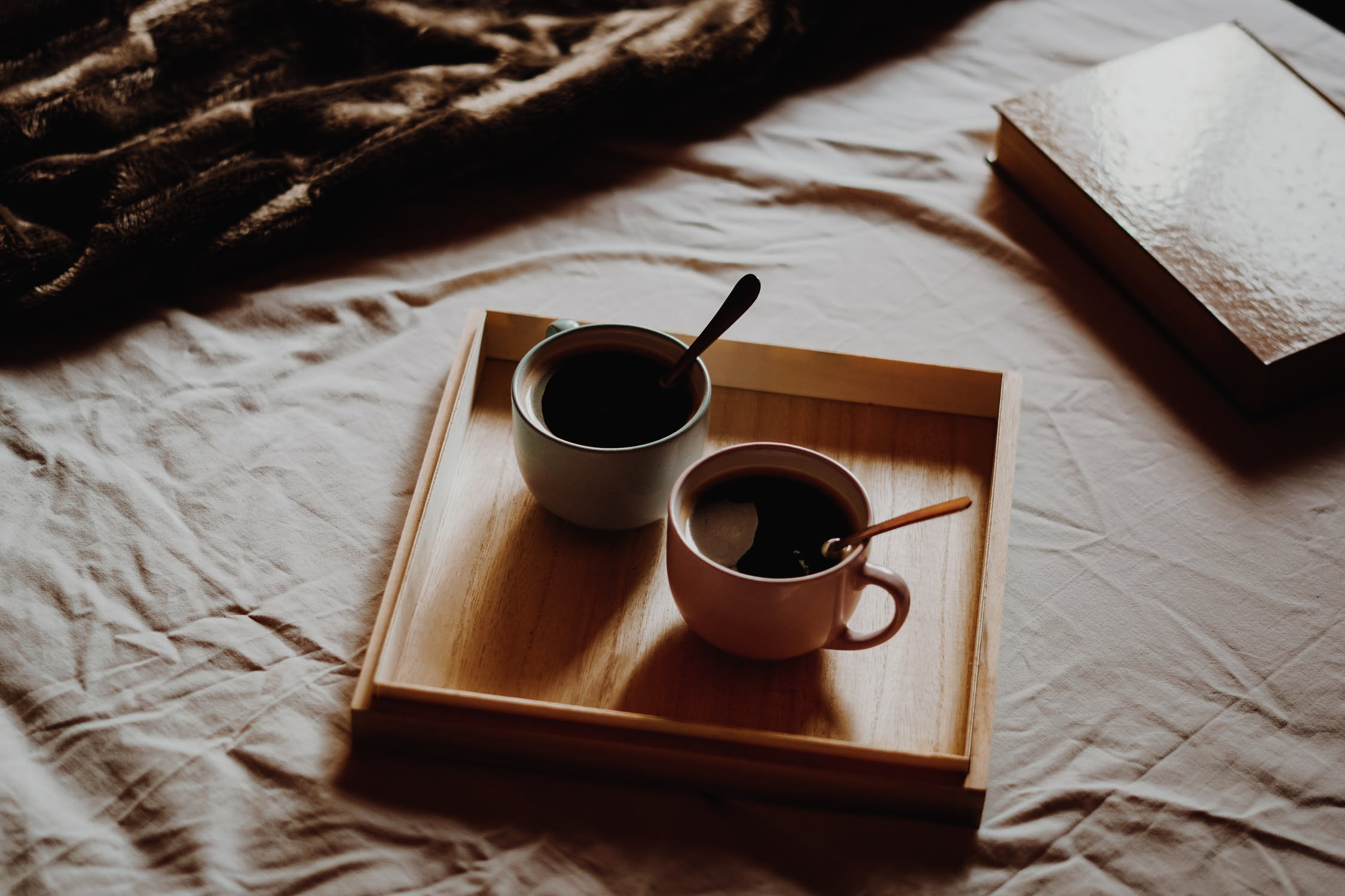 2 cups of coffee on a little platter next to a book