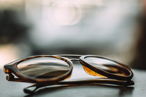 Close-up Photography of Brown Framed Sunglasses on Gray Surface