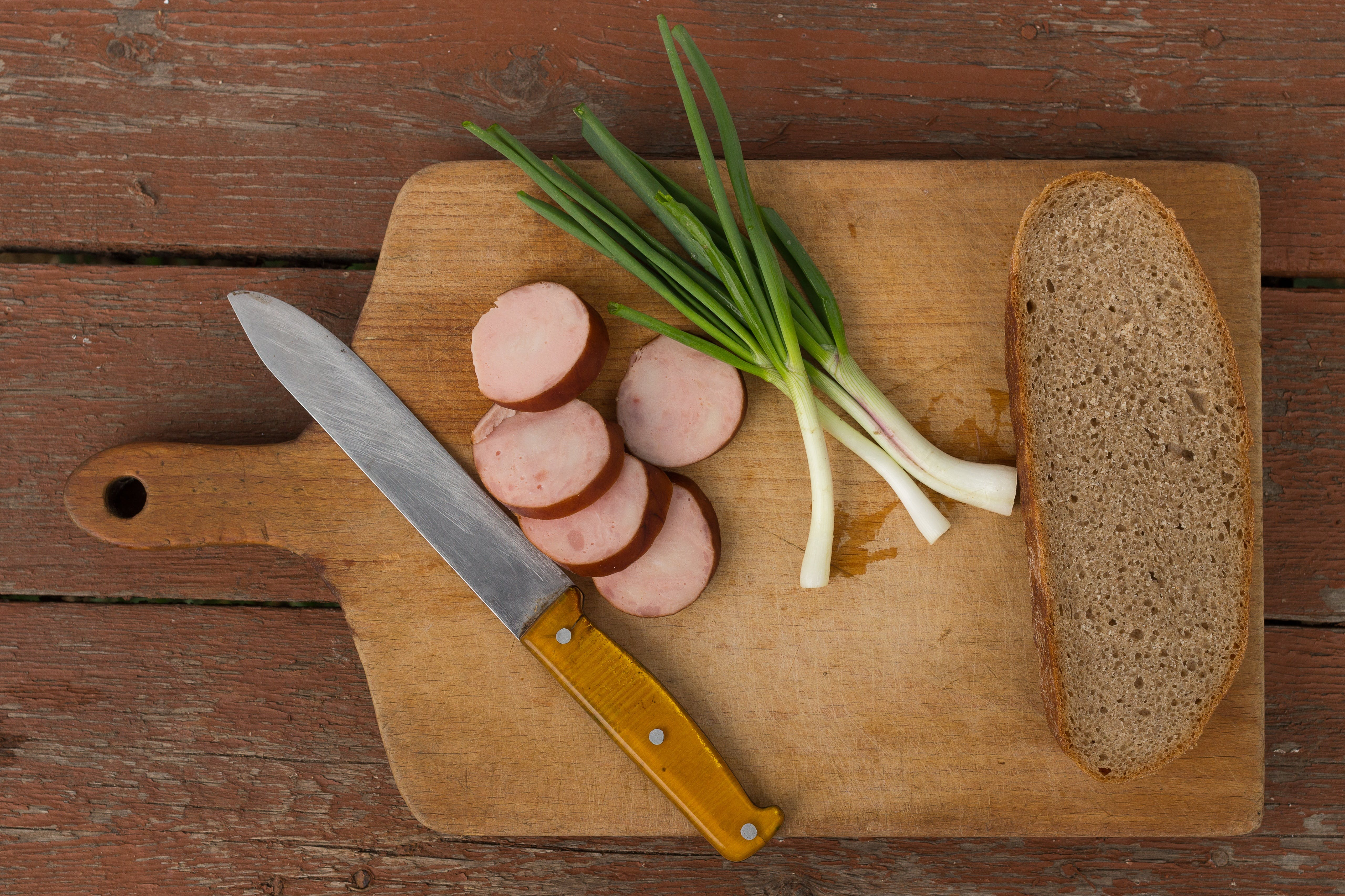 Kitchen Knife Next to Slice Bread on Chopping Board