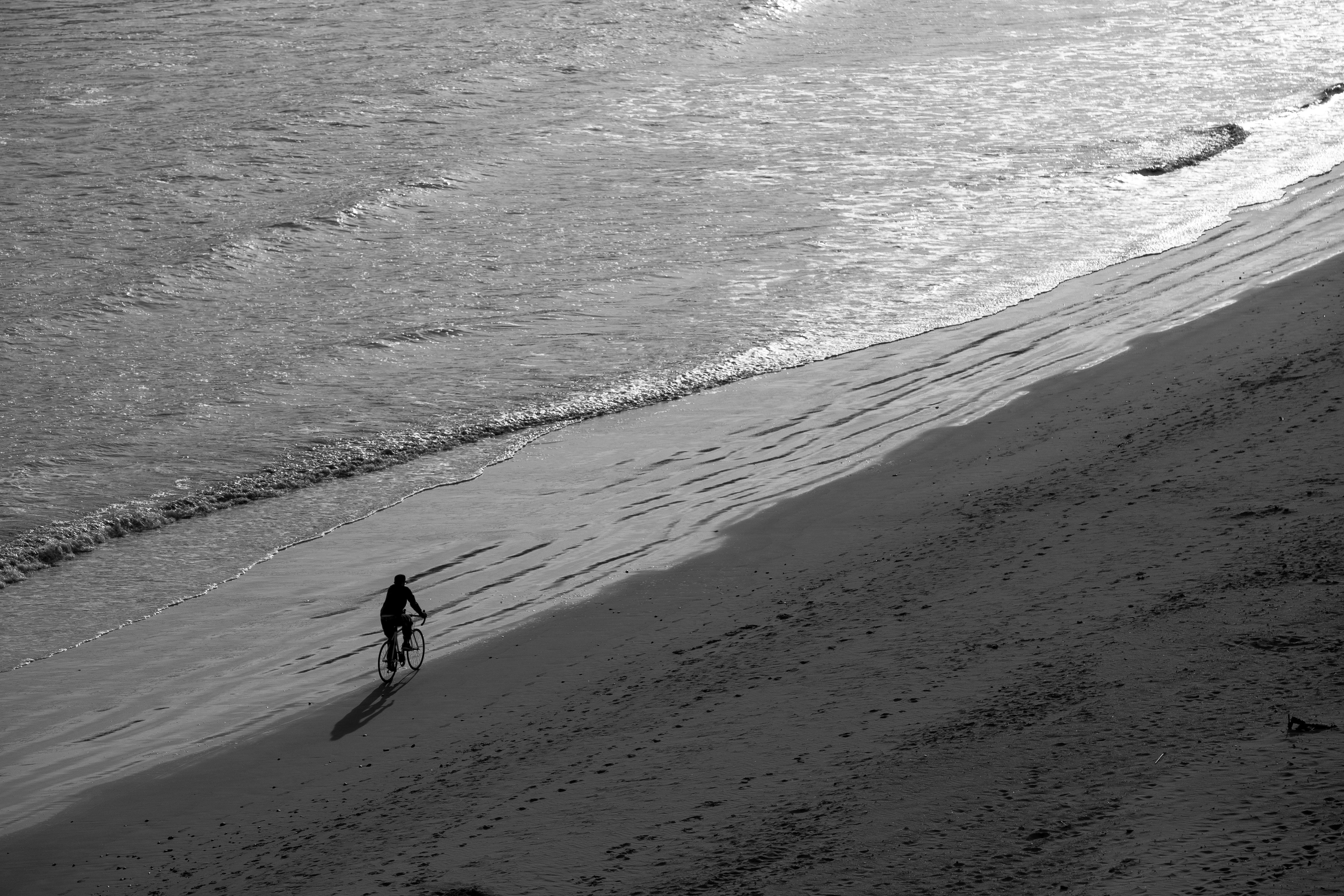 Man Riding Bike on Seashore