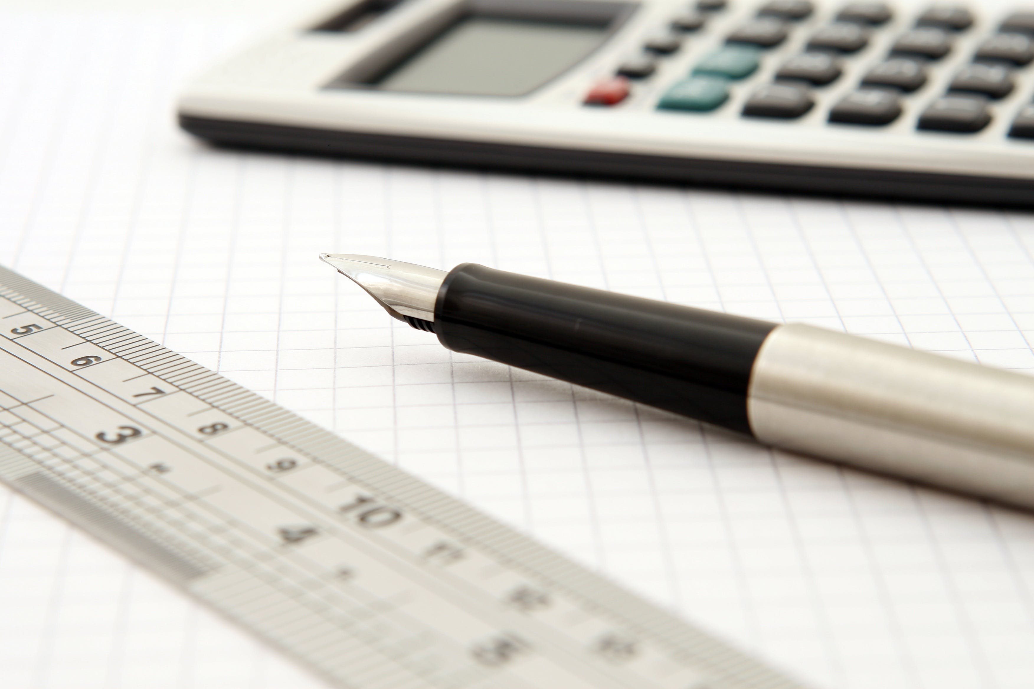 Shallow Focus of Silver and Black Fountain Pen Beside Ruler and Scientific Calculator