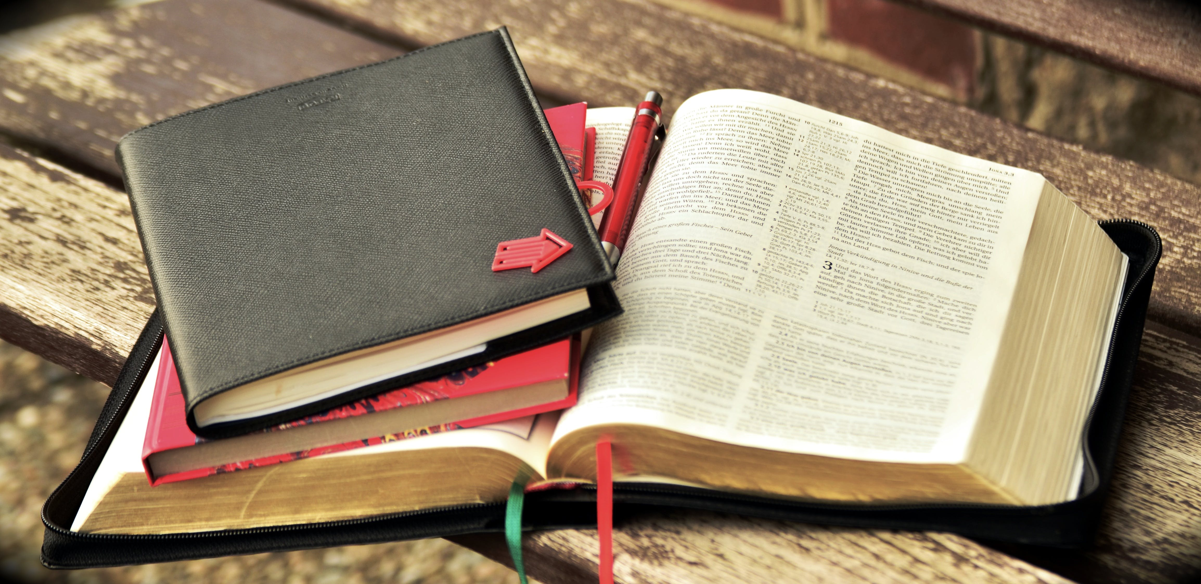 Black Leather Notebook With Red Arrow on Cover on Red Bookm and Bible