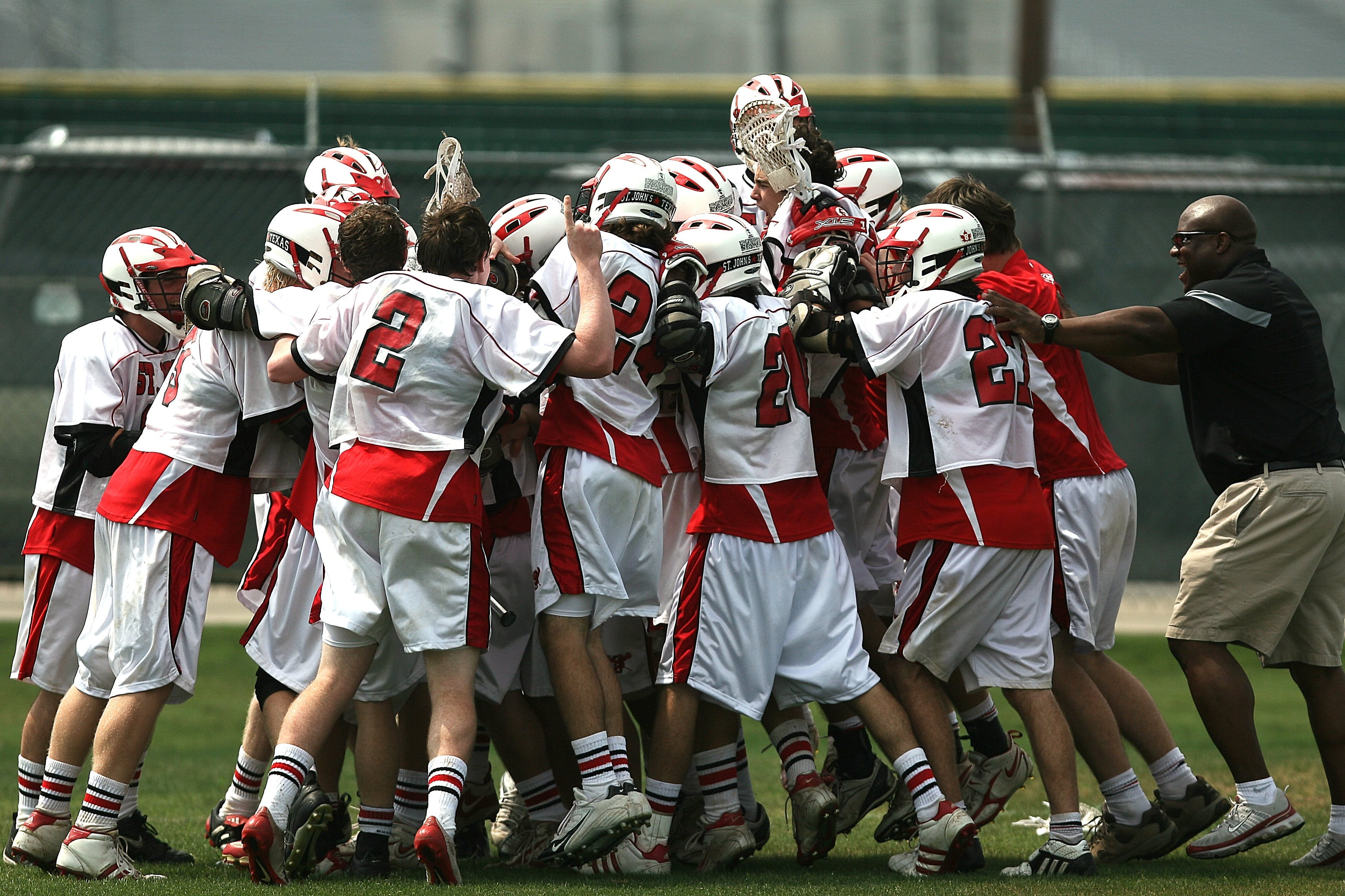 Group of Lacrosse Players Celebrating With Coach during Daytime