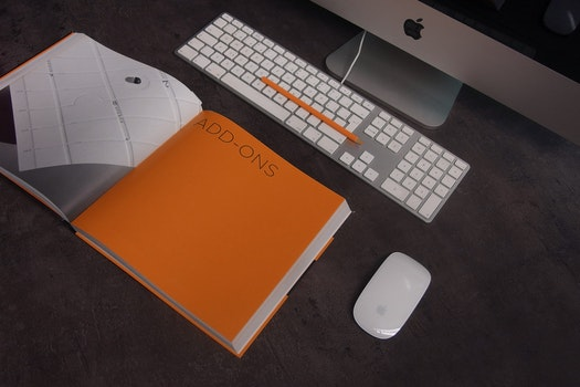 Orange Book in Distance With Silver Imac