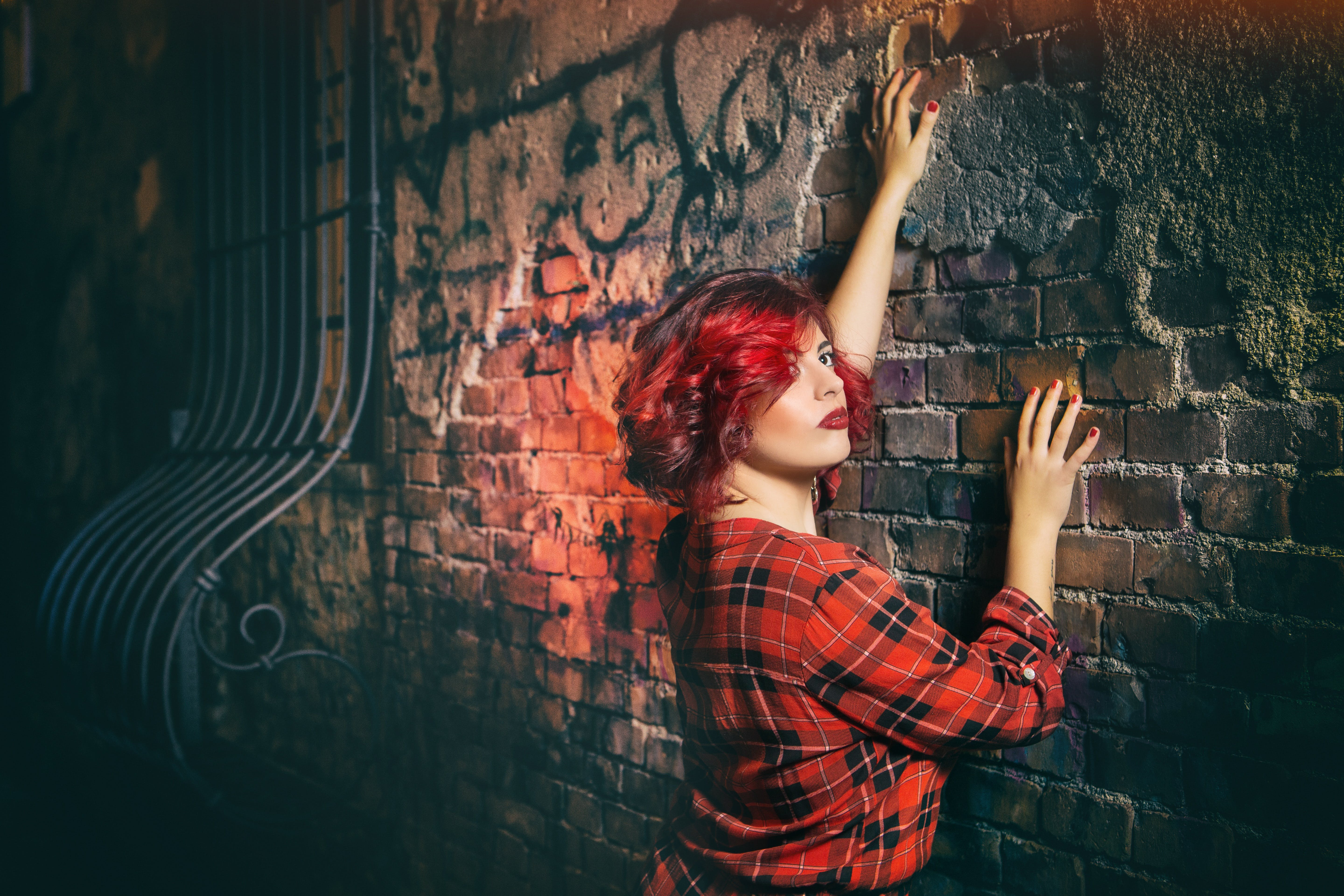 Woman in Red Black and White Plaid Holding Gray Concrete Wall