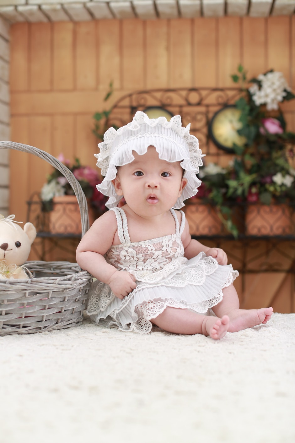 Baby Wearing White Headband and White Lace Floral Dress Sitting Beside Gray Wicker Basket