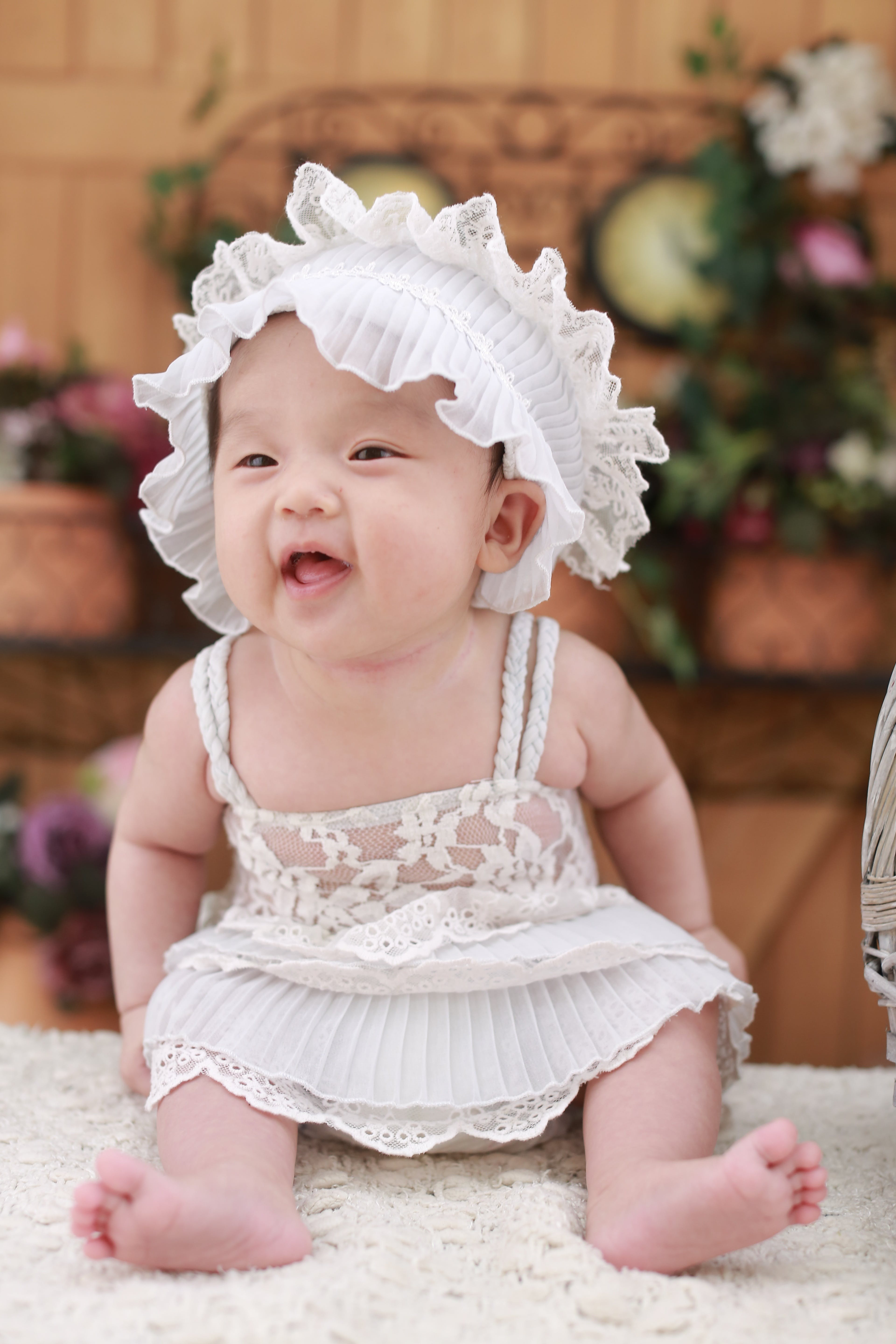 Baby in White Dress With White Headdress