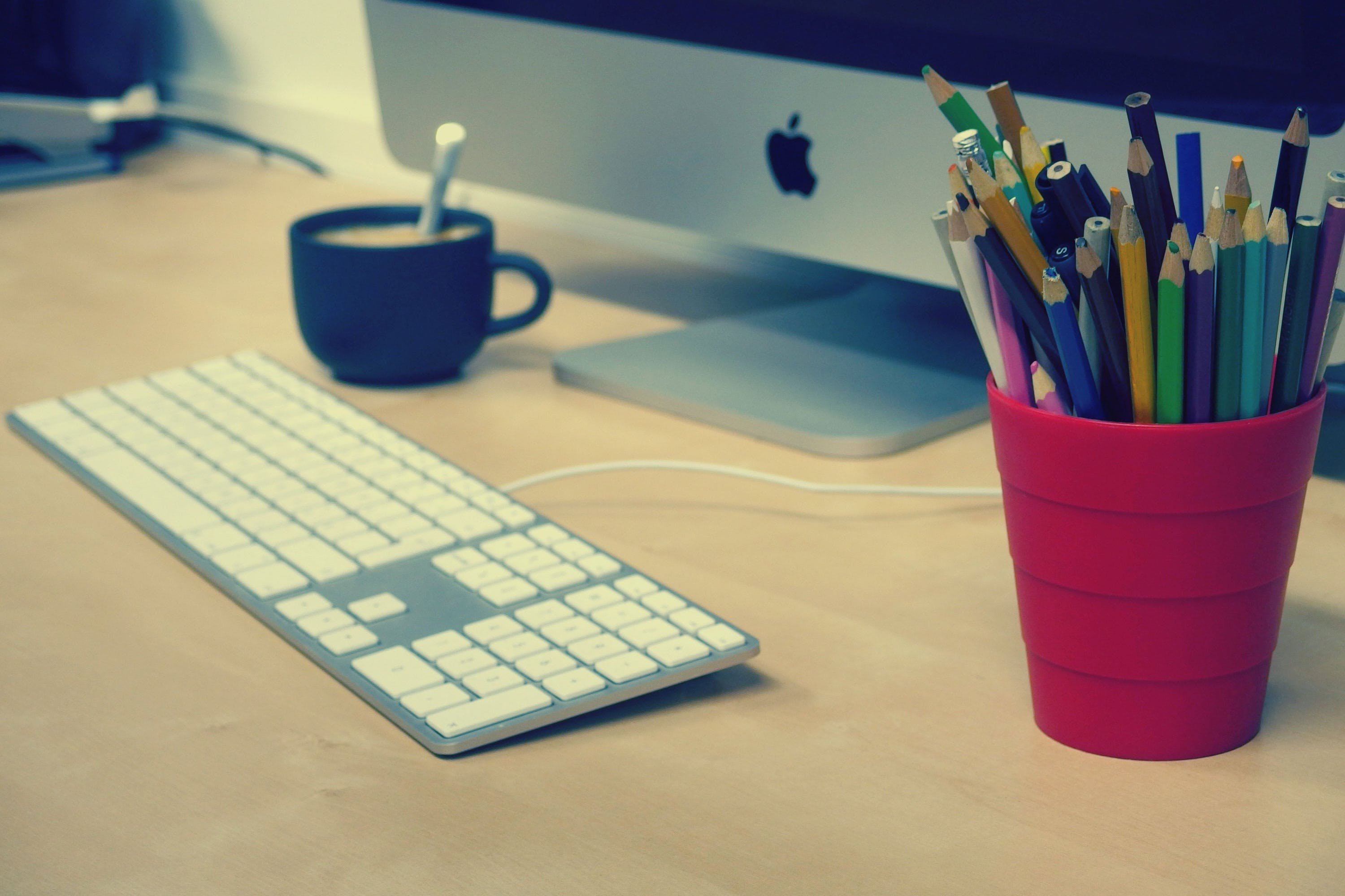 Blue Green and Black Colored Pencils on Red Plastic Cup Beside Silver Imac