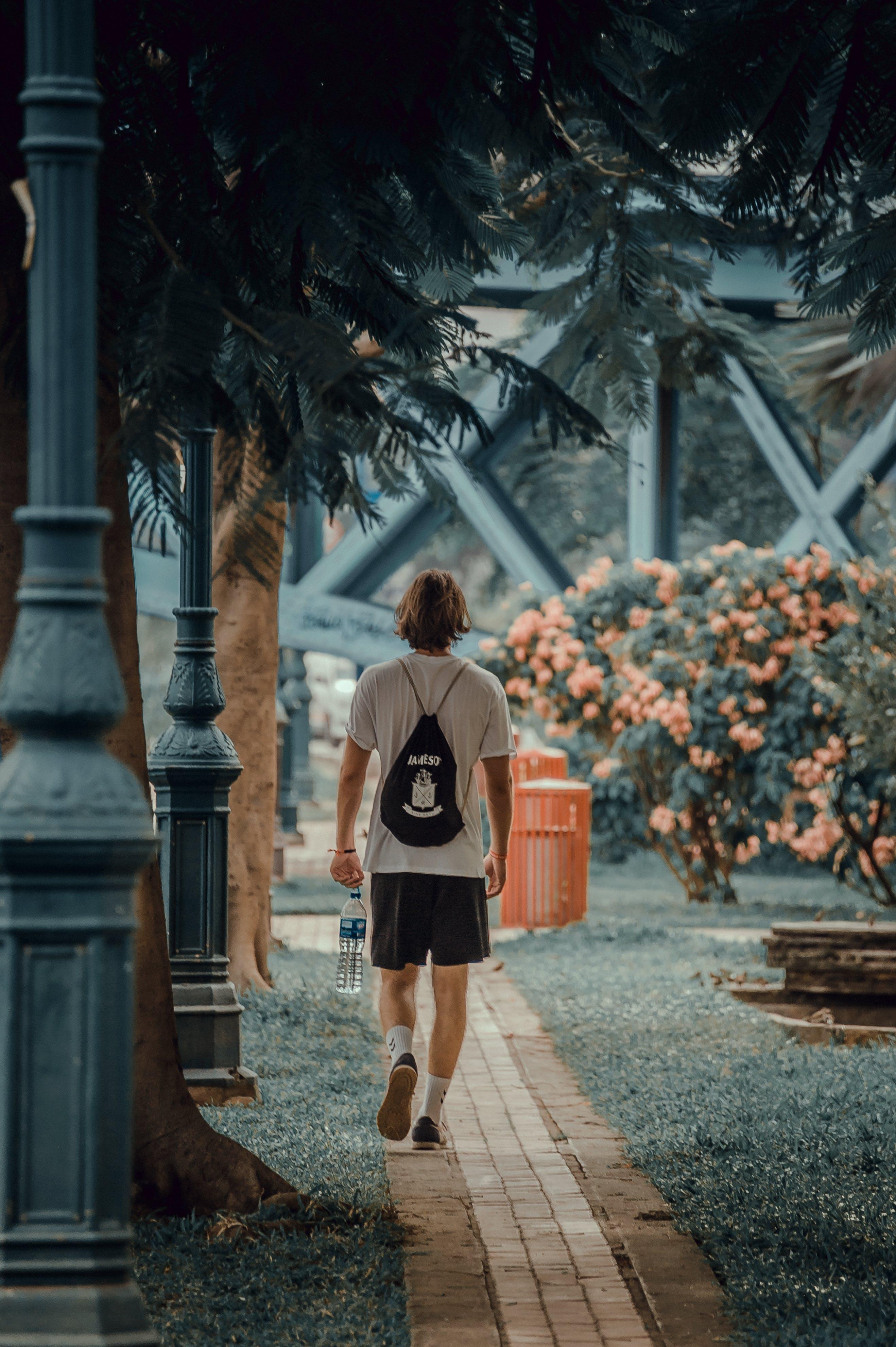 Photo of Man Walking on Pavement