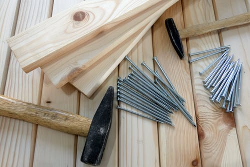 Gray Nails Beside Beige Wooden Planks and Hammers