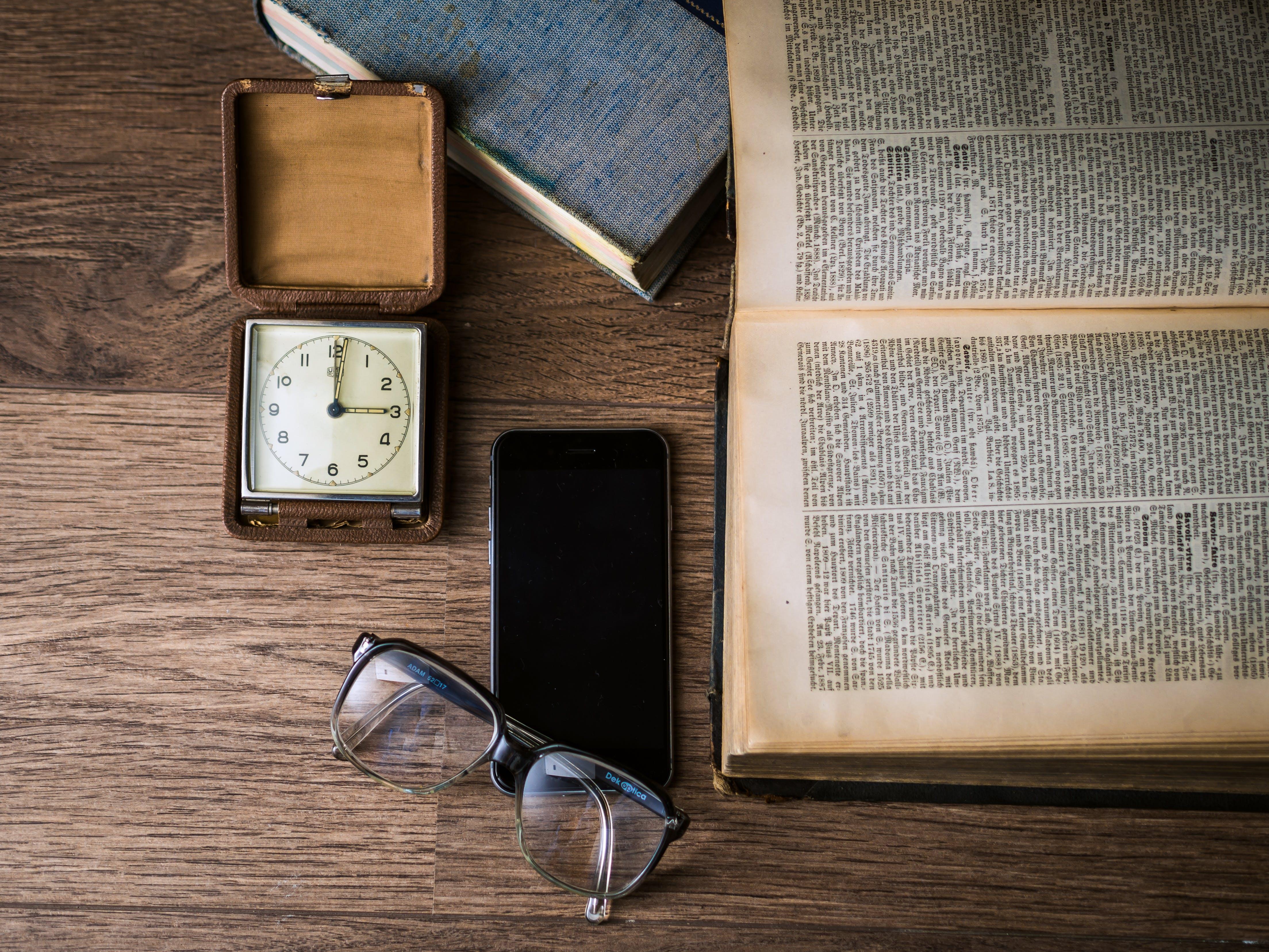 Black Framed Eyeglasses on Top of Black Smartphone Near Brown Square Analog Clock on Brown Wooden Surface