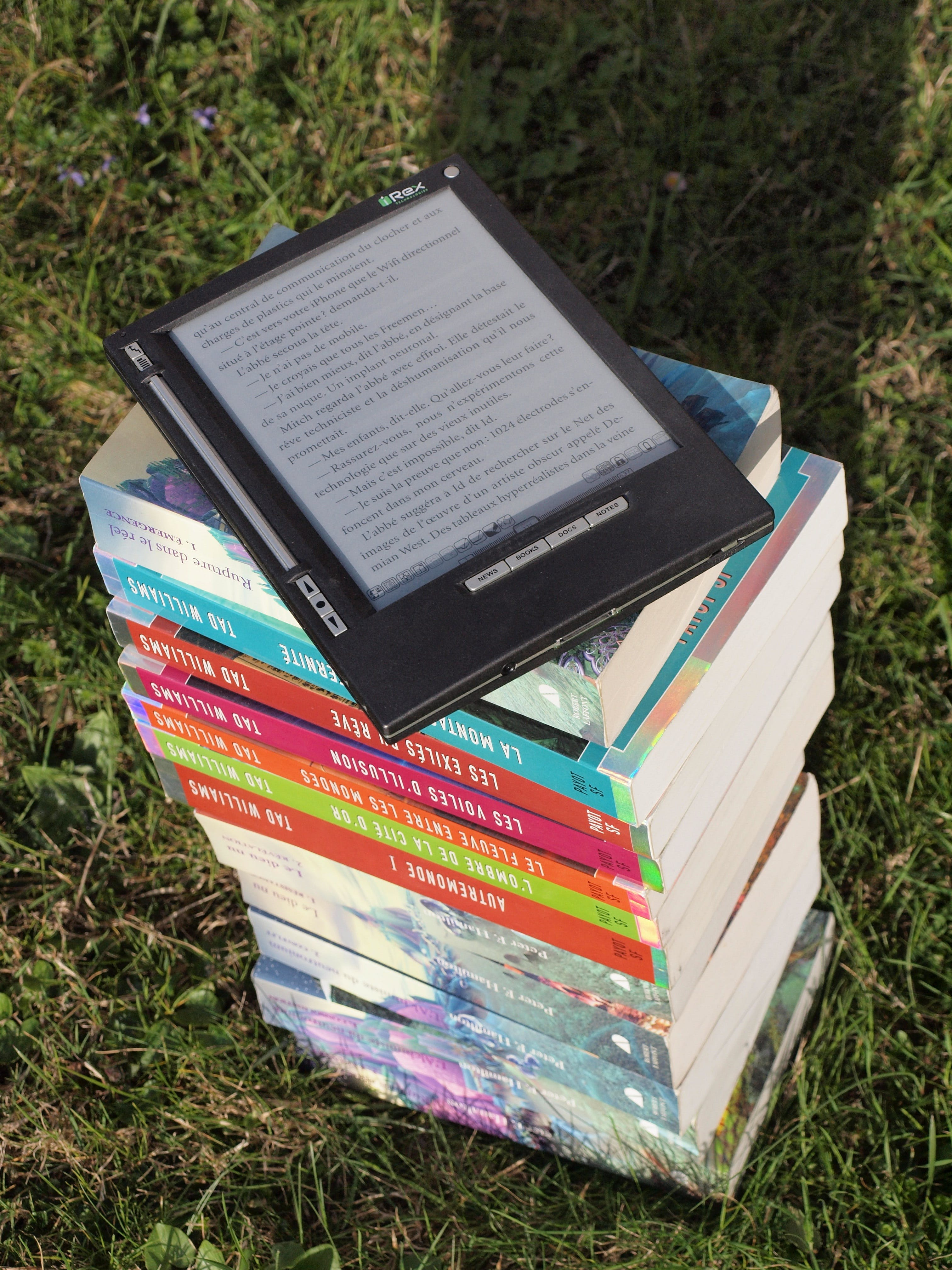 Blue Pink Gray and Green Labeled Hardbound Book Pile on Green Grass during Daytime