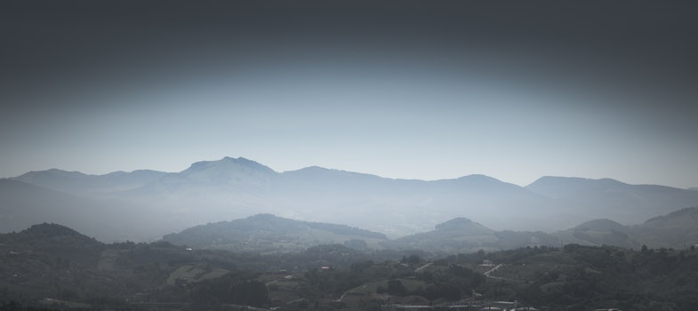 Greyscale Photo of Mountains With Mist
