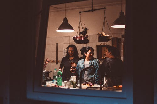 Three Women Standing Inside Room With Lights Turned on