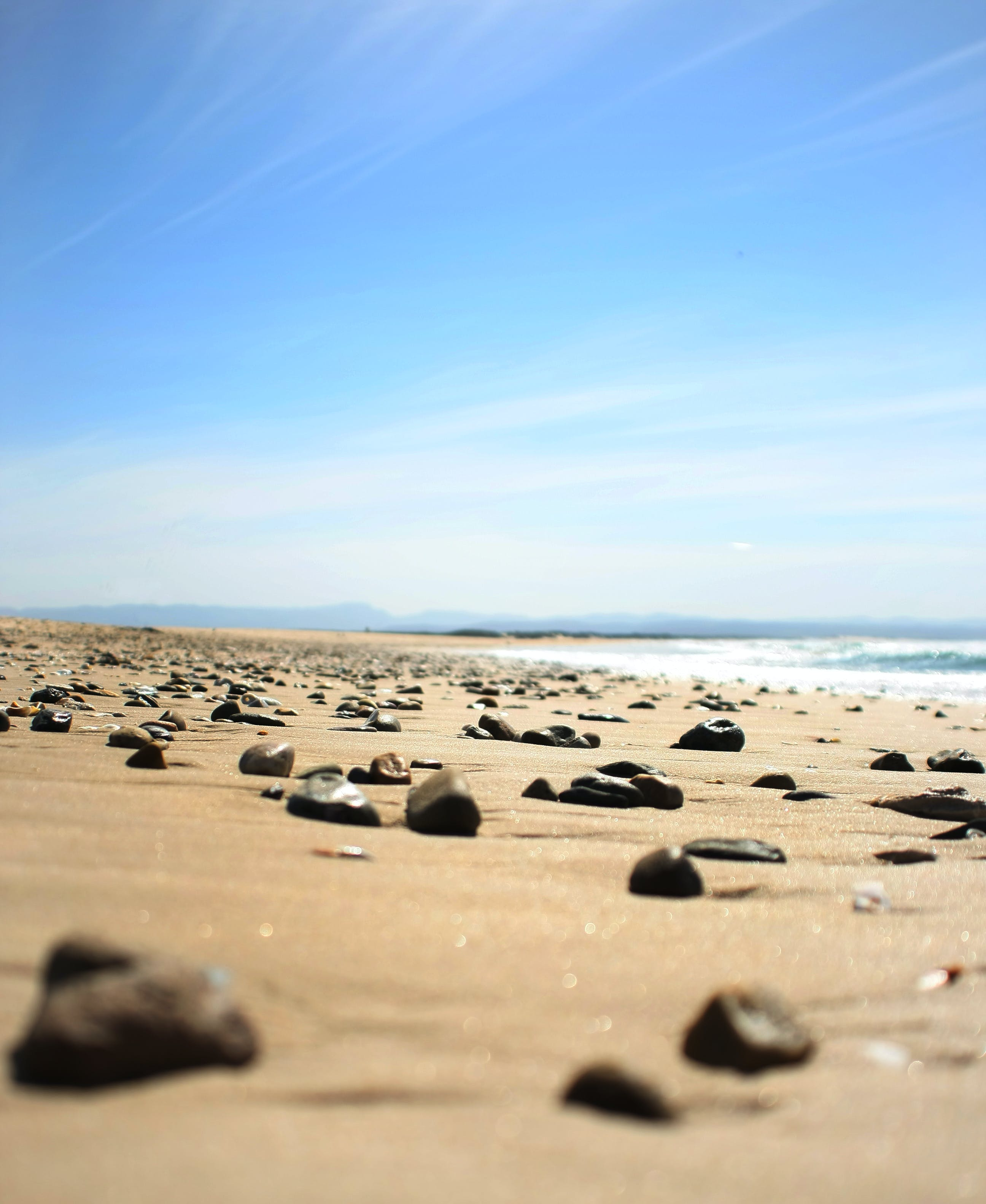 Brown Sand Seashore With Brown Pebbles Under White and Blue Cloudy Skies